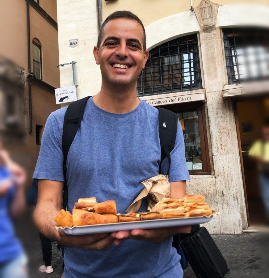 A Secret Food Tour of Rome guide delivers some pizza to his guests.
